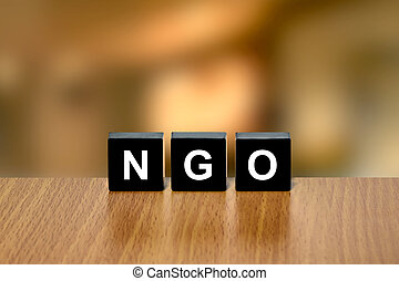 NGO or non-governmental organization on black block with...