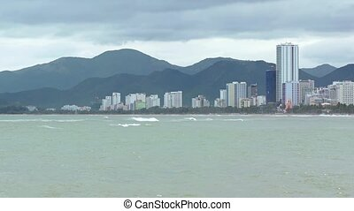 Cityscape of Nha Trang, Vietnam, stands against a background of low, forested hills, and over a tropical beach on an overcast day.