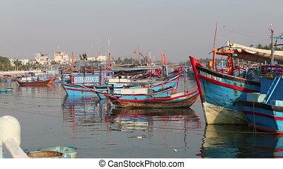 fishing boats moor by city embankment at dawn
