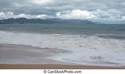 Gentle waves break over a sandy beach in Nha Trang on a cloudy day.
