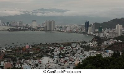 Holiday resort Nha Trang Vietnam high definition time lapse on a cloudy day from a view point north of the city. With the mountains in the background and the south china sea to the left.