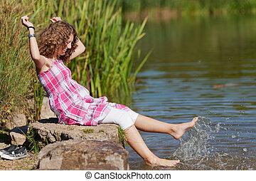 niña, con, armamentos levantaron, sentado, en, roca, mientras, salpicar el agua