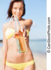niña, con, botella, de, bebida, en la playa