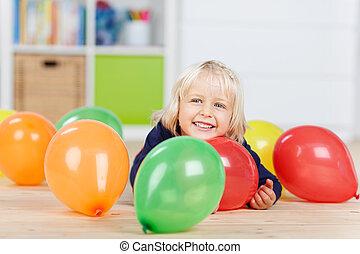 niña, con, globos coloridos, yacer piso