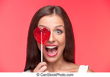 niña, con, lollipop., retrato, de, hermoso, mujer joven, tenencia, forma corazón, chupete, delante de, ella, ojo, mientras, aislado, en, rojo