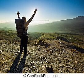 niña, con, manos arriba, en las montañas, contra, sol