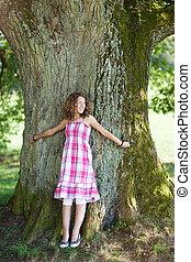 niña, con, pelo rizado, estantes, delante de, un, árbol