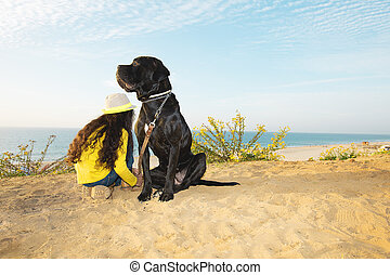 niña, con, un, perro, sentado on the beach