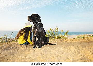 niña, con, un, perro, sentado on the beach