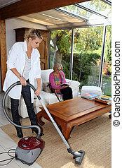 niña, el limpiar con la aspiradora, para, un, mujer anciana
