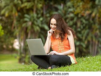 niña, el sentarse en el parque, con, un, computador portatil