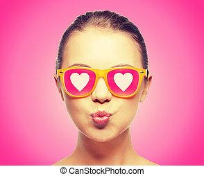 niña, en, rosa, gafas de sol, beso que sopla