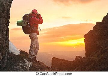 niña, fotógrafo, con, un, mochila, en las montañas, tomar fotografías, de, el, ocaso