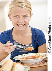 niña joven, dentro, comida, sopa, sonriente