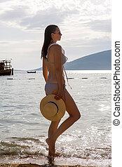 niña joven, en, un, traje de baño, estar de pie on the beach, en, ocaso