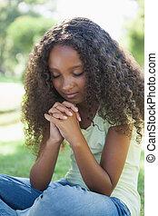 niña joven, rezando, en el parque