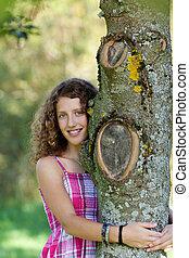 niña joven, se abrazar, árbol, en el estacionamiento