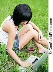 niña joven, sentado, en, un, parque, con, computadora de computadora portátil