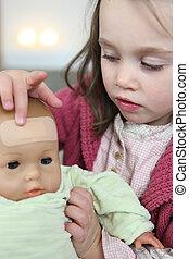 niña, poniendo, un, yeso, en, ella, bebé, muñeca, frente