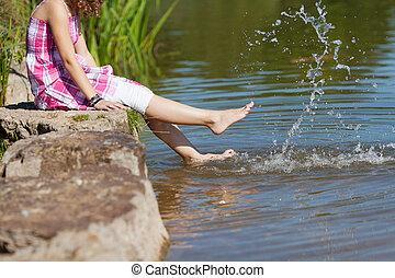 niña, sentado, en, roca, mientras, salpicar el agua