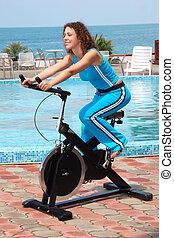 niña sonriente, en, bicicleta, entrenamiento, aparato, al aire libre