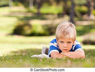 niño, acostado, en el parque