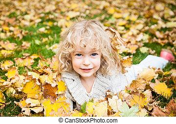 niño, acostado, en, otoño sale