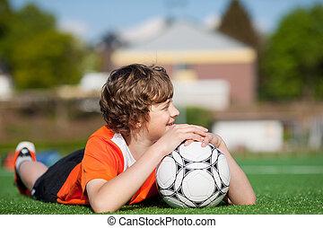 niño, con, futbol, acostado, en, campo, mientras, el mirar lejos