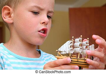niño, con, modelo, de, barco, en, manos