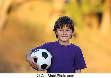 niño, con, pelota del fútbol, en, ocaso
