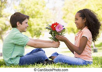 niño, dar, niña joven, flores, sonriente