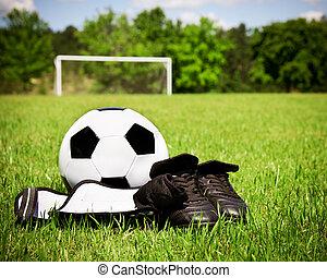 niño, deportes, concepto, con, pelota del fútbol, cleats, espinilla, guardias, en, campo, con, espacio de copia