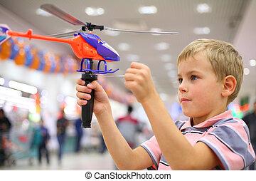 niño, en, tienda, con, juguete, helicóptero