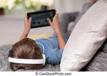 niño joven, acostado, escuchar música, en, el suyo, tableta