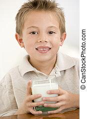 niño joven, dentro, leche de bebida, sonriente
