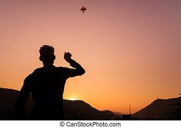 niño joven, juego, con, cometa, en, sunset., iluminar desde el fondo, colorido, cielo, vista trasera, rajasthan, india.