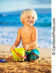 niño joven, juego, en la playa
