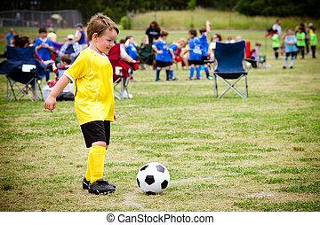 niño joven, niño, jugar al fútbol, durante, organizado,...