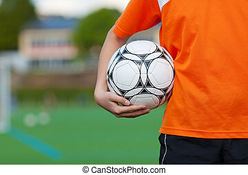 niño joven, pelota del fútbol de valor en cartera