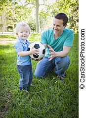 niño joven, y, papá, juego, con, pelota del fútbol, en el estacionamiento