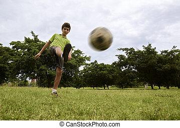 niño, jugar al balompié, y, juego del fútbol, en el estacionamiento