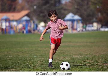 niño, jugar al fútbol, en el parque