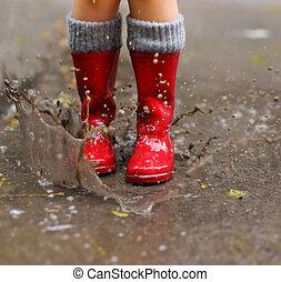 niño, llevando, rojo, botas de lluvia, saltar, en, un,...