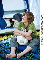 niño, pelota del fútbol de valor en cartera, delante de, tienda
