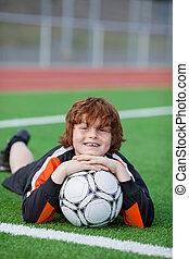 niño pequeño, con, futbol, acostado, en, campo