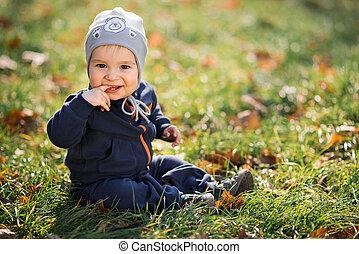 niño pequeño, el sentarse en la hierba
