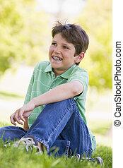 niño, sonriente, sentado, joven, aire libre
