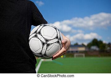 niño, sostener la bola, en, campo del fútbol