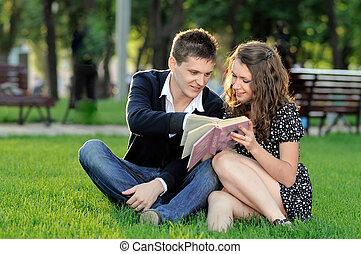 niño y niña, leer un libro, el sentarse en la hierba
