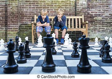 niños, al aire libre, jugando al ajedrez